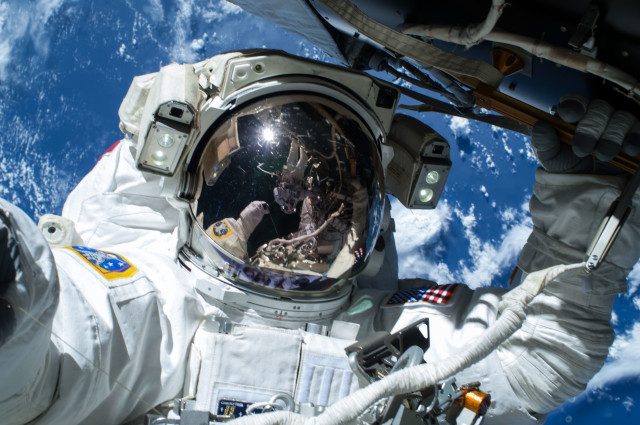 NASA astronaut Barry Wilmore is shown here working outside the International Space Station on 2/21/15.  He and fellow spacewalker Terry Virts – who can be seen reflected in Wilmore's visor – were preparing the ISS for future arrivals by U.S. commercial crew spacecraft.  (NASA)