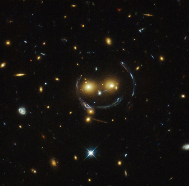 "Although it looks like the iconic ""Have a Nice Day"" smiley face, this is actually the galaxy cluster SDSS J1038+4849 as imaged by the Hubble Space Telescope.  The two eyes in the image, released on 2/10/15, are really two very bright galaxies and the smile lines are arcs caused by strong gravitational lensing. (NASA/ESA)"