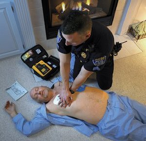 An EMS technician performs CPR on a cardiac arrest patient.  Behind patient is an automated external defibrillator (AED) which is also used to help stop ventricular fibrillation (David Bruce Jr./Creative Commons)