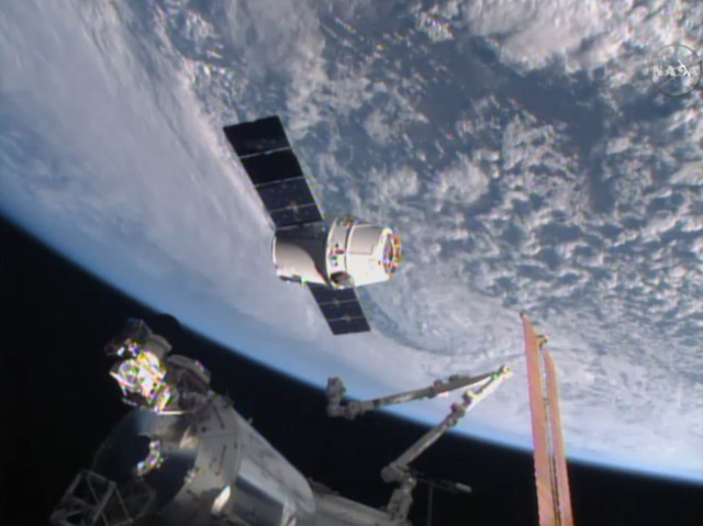 The Dragon spacecraft, seen here in this image from NASA-TV, is about to be grappled by the International Space Station's robotic arm as it arrives on 4/16/15.  The cargo ship delivered nearly 2,000 kg of food, science experiments, equipment and the first espresso maker in space to the 6 ISS crewmembers (NASA)