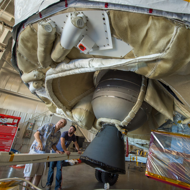 "Investigators with the Low-Density Supersonic Decelerator Project (LDSD) at NASA's Jet Propulsion Laboratory are seen inspecting the LDSD spacecraft on 5/28/15.  The space vehicle that's been dubbed the ""flying saucer"" is used to test new technologies that will allow the space agency to safely land heavier spacecraft such as those that would be used for future manned missions to Mars.  (NASA)"