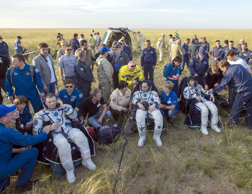 "Members of the International Space Station's ""Expedition 43"" take a rest break shortly after landing safely in the steppes of Kazakhstan on June 11, 2015.  The returning crew members are (L-R) Terry Virts of the U.S., Anton Shkaplerov of Russia and Samantha Cristoforetti of Italy. The trio spent 199 days aboard the space station. (NASA)"