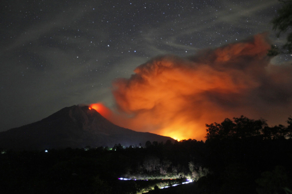 Indonesia's Mount Sinabung spews volcanic materials and hot molten lava from its crater on June 25, 2015. (AP)