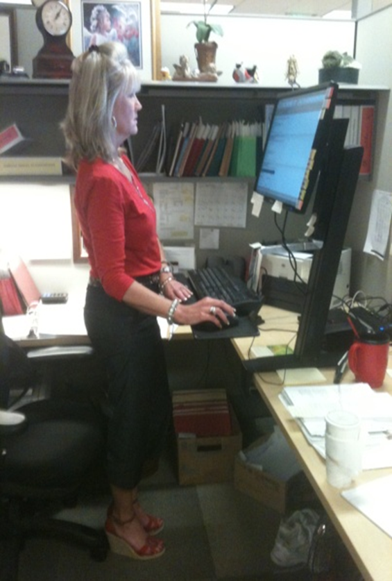 A woman using a sit-stand desk in its standing configuration. (National Institute for Occupational Safety and Health)