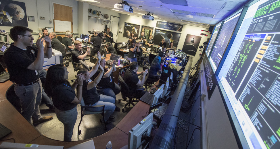 New Horizons Flight Controllers celebrate after they received confirmation from the spacecraft that it had successfully completed the flyby of Pluto, Tuesday, July 14, 2015 in the Mission Operations Center (MOC) of the Johns Hopkins University Applied Physics Laboratory (APL), Laurel, Maryland. (NASA/Bill Ingalls)