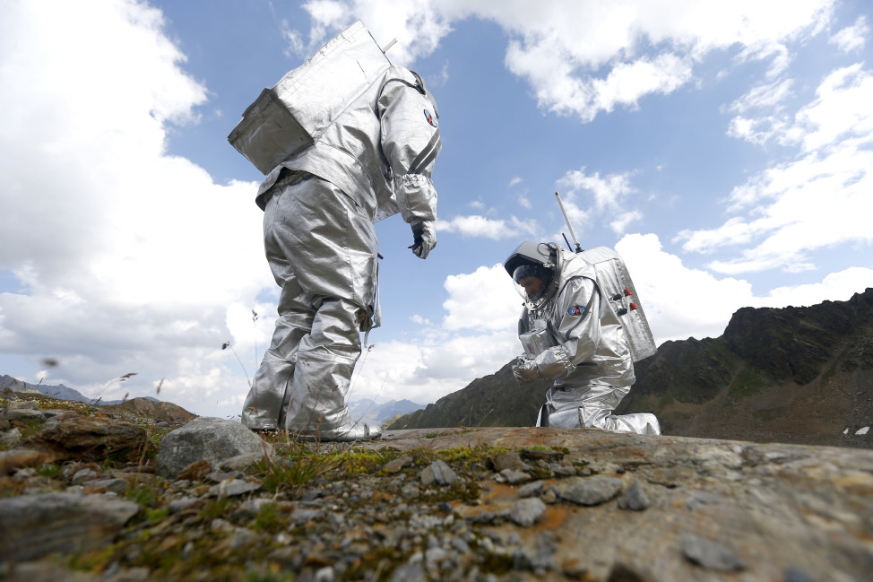 Inigo Munoz Elorza of Spain (L) and Stefan Dobrovolny of Austria (R) take stone samples on 8/7/15 during a simulated Mars mission on Tyrolean glaciers in Kaunertal, Austria.  The Austrian Space Forum sent some of its researchers to practice weight-less walking in spacesuits on a glacier which resembles the terrain on Mars.  (Reuters)