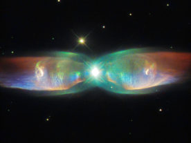 The shimmering colors visible in this NASA/ESA Hubble Space Telescope image, released 8/24/15, shows off the remarkable complexity of the PN M2-9 Twin Jet Nebula which is also known as Minkowski's Butterfly, the Wings of a Butterfly Nebula or simply Butterfly Nebula. The luminous nebula is about 2,100 light-years away from Earth. Unlike ordinary planetary nebulae which has one star at their center, this is a bipolar nebula which has two stars from a binary star system. (ESA/Hubble & NASA)