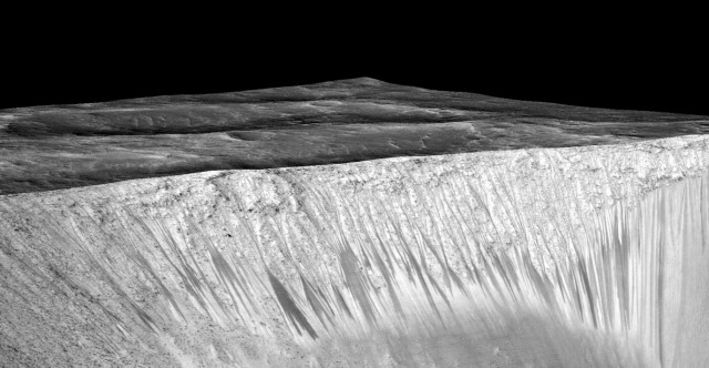Dark narrow streaks called recurring slope lineae emanating out of the walls of Garni crater on Mars. The dark streaks here are up to few hundred meters in length. They are hypothesized to be formed by flow of briny liquid water on Mars. (NASA/JPL/University of Arizona)