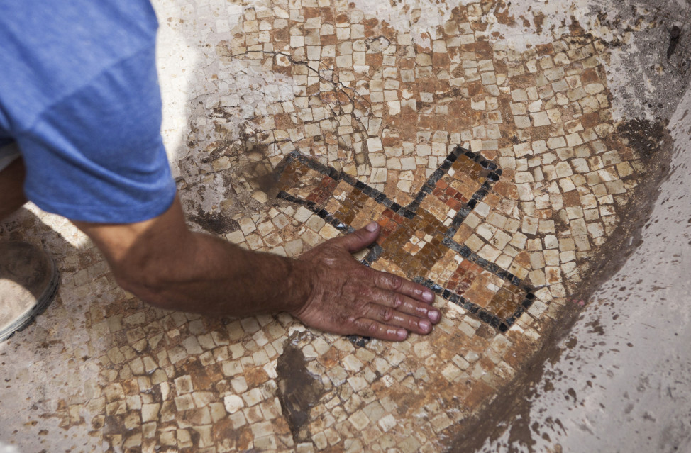 A worker for the Israel Antiquities Authority shows a cross that was designed on a mosaic floor of a Byzantine era burial site at Ben Shemen Forest on 9/21/15. Investigating archaeologists say that may have marked the burial spot of an important person. (AP)