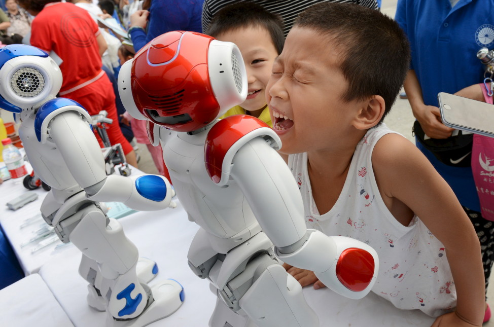 A boy tries to talk with a humanoid robot during a science event in the Chinese province of Henan province on 9/19/15. (Reuters)