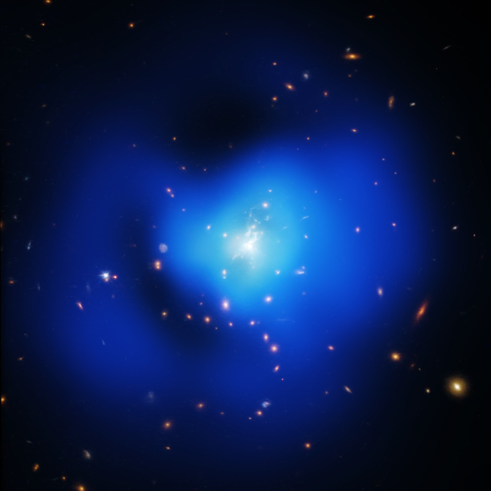 "This photo of the ""Phoenix Cluster"", released on 9/30/15, is actually a composite of images of the galaxy cluster taken at X-ray, optical, and ultraviolet wavelengths by NASA's Chandra X-ray Observatory, the Hubble Space Telescope, and the Clay-Magellan telescope located in Chile.  (NASA/CXC/MIT/M.McDonald et al; NASA/STScI; TIFR/GMRT)"