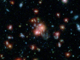 SpARCS1049+56 is a massive cluster of galaxies that creates hundreds of new stars each year. It's pictured here in this multi-wavelength view from NASA's Hubble and Spitzer space telescopes. (NASA/STScI/ESA/JPL-Caltech/McGill)