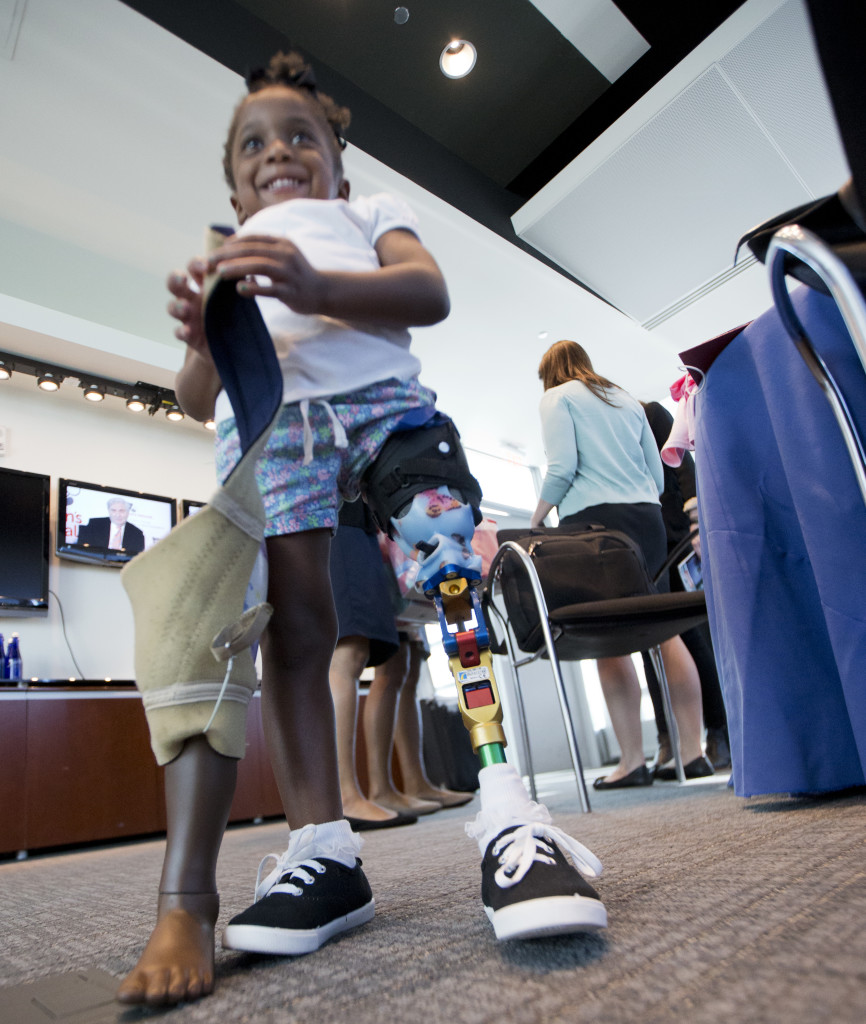 Little three year-old Miyah Williams holds her old leg prosthesis as she wears a new and more high-tech version that was attached several months earlier. Miyah was at a 10/23/15 meeting in Washington, DC that discussed problems with pediatric prosthetic devices. (AP)