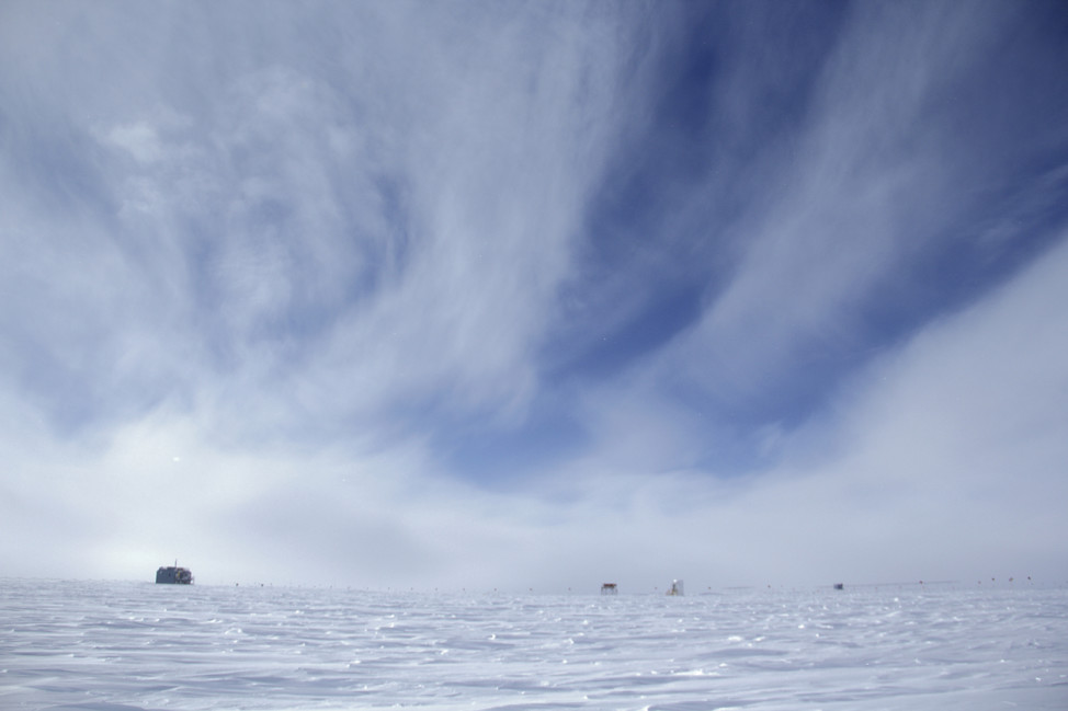 A vast, empty landscape  surrounds the Atmospheric Research Observatory (ARO) at the South Pole. The upwind side of the station (left) is the clean air sector. (Photo by Hunter Davis)