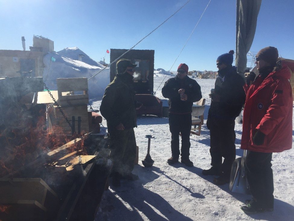 Berming Man volunteers gather outside to enjoy an open fire, a rare sight at the South Pole. (Photo by Refael Klein)