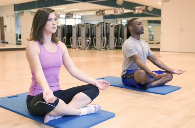 Two Yoga class participants assume a cross-legged, palms up meditation position. (CDC/Creative Commons)