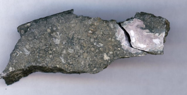 This close-up picture shows a ceramic-like refractory inclusion (pink inclusion) still embedded into the meteorite in which it was found. (Origins Lab, University of Chicago)