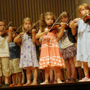Children playing violin in a group recital at a Suzuki Institute (Stilfehler via Wikimedia Commons)