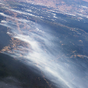The smoke from multiple fires in the Mato Grosso region of Brazil rises over forested and deforested areas in this astronaut photograph taken from the International Space Station on August 19, 2014. International Space Station (NASA)