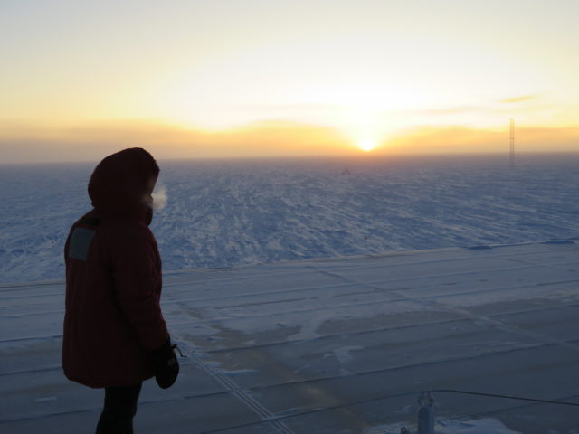From atop the roof of Amundsen-Scott station, a South Pole winterover watches the sun break the horizon. (Photo: Scott Deaton)