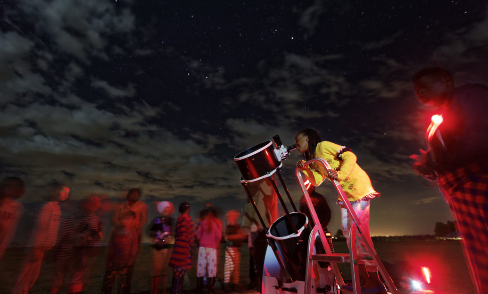 In this photo taken 2/3/17, a student looks up at the moon through a telescope, during a visit by The Traveling Telescope at St Andrew's School near Molo in Kenya's Rift Valley. The Traveling Telescope visits some of the country's most remote areas with telescopes and virtual reality goggles. (AP)