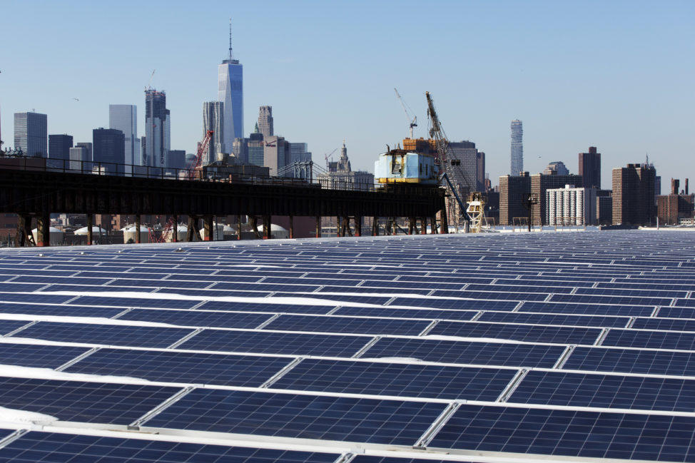A rooftop is covered with solar panels at the Brooklyn Navy Yard, 2/14/17, in New York City, you can see the Manhattan skyline is at top. According to the New York City Mayor's office, these new panels will generate 1.1 million kilowatt hours of energy per year. (AP)