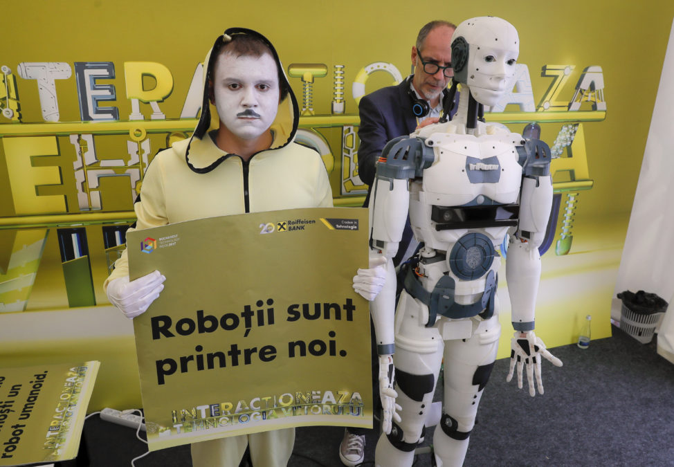 "French designer Gael Langevin stands behind the InMoov robot after he unveiled it May 26 at a technology fair in Bucharest, Romania. Langevin says the robot can be programmed to speak English, Spanish, French, Russian and Dutch, with a basic model costing about 1,500 euros. An entertainer seen standing on the left of the robot holds a sign that reads ""The robots are among us"". (AP)"