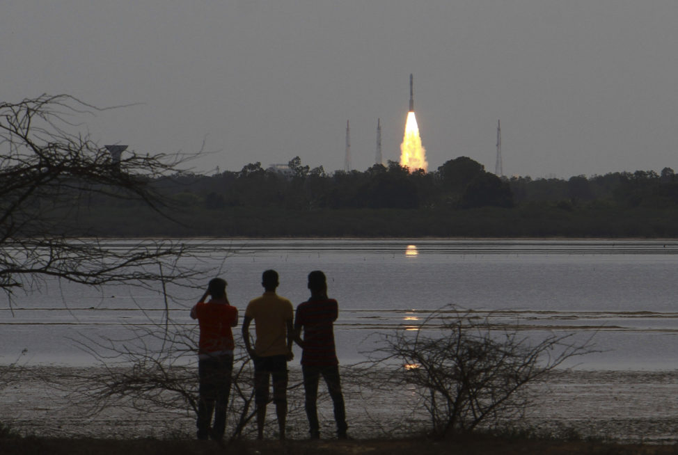 People watch as Indian Space Research Organization (ISRO)'s Polar Satellite Launch Vehicle carrying the 712 kg Cartosat-2 Series Satellite along with 30 co-passenger satellites, blasts off from the Satish Dhawan Space Centre at Sriharikota in Andhra Pradesh, around 117 kilometers (72 miles) northeast of Chennai, India, Friday, June 23, 2017. (AP)