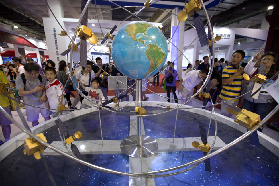 People visiting the China Beijing International High-Tech Expo in Beijing, Saturday, June 10, 2017 are seen here looking at a mockup of China's homegrown Beidou satellite navigation system. (AP)