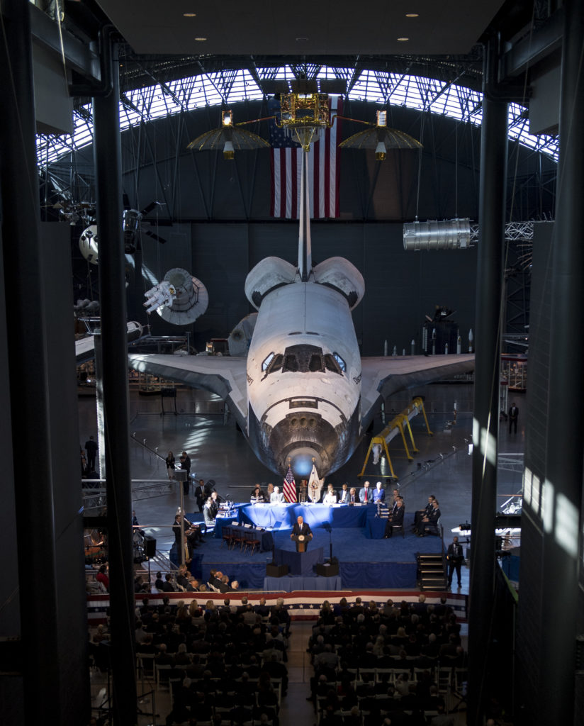 With NASA's Space shuttle Discovery as a backdrop, U.S. Vice President Mike Pence delivers his opening remarks during the National Space Council's first meeting, 10/05/17 at the Smithsonian National Air and Space Museum's Steven F. Udvar-Hazy Center in Chantilly, Va. (NASA/Joel Kowsky)