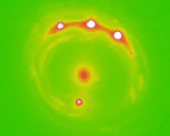 Image of the gravitational lens RX J1131-1231 galaxy with the lens galaxy at the center and four lensed background quasars. University of Oklahoma research estimate that there are trillions of planets in the center elliptical galaxy in this image. (University of Oklahoma)