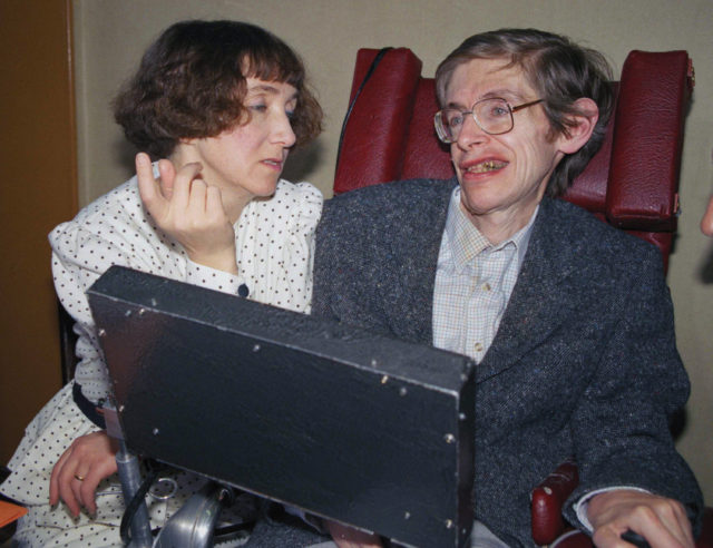 In this March 3, 1989 file photo astrophysicist Dr. Stephen Hawking, then 47, answers questions with the help of his computer and the assistance of his then wife Jane, in Paris. (AP Photo/Lionel Cironneau, File)