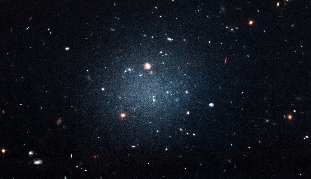 "This is a galaxy that's been catalogued as NGC 1052-DF2. Astronomers call it the ""see-through"" galaxy since you can see right through it and observe other and more distant galaxies behind it. Researchers have found that the galaxy is missing most, if not all, of its dark matter. (NASA, ESA, and P. van Dokkum (Yale University))"