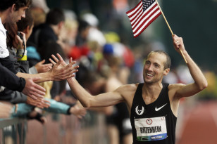 Dathan Ritzenhein waves the American flag after qualifying for the USA's 2012 Olympic team in the 10,000 meters. Photo: AP