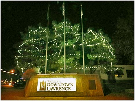 "Christmas lights illuminate the ""Welcome to Downtown Lawrence"" sign"
