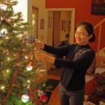 Chun Guo hangs an ornament on the Christmas tree