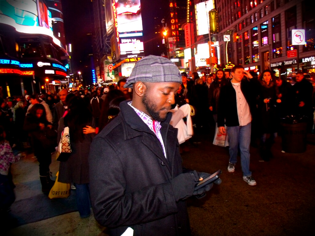 "Alex updates his Facebook status while visiting Times Square in New York. He says, ""I was supposed to be on holiday :)"""