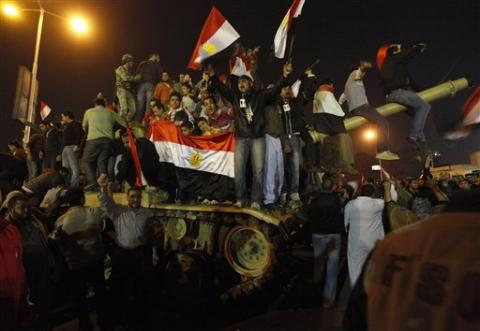 Egyptian citizens stand on an Egyptian military tank as they celebrate after President Hosni Mubarak resigned and handed power to the military at Tahrir Square in Cairo, Egypt, February 11, 2011 (Photo: AP)