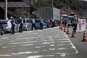 Police officers stop cars at a checkpoint near the town of Namie, Fukushima Prefecture (Photo: AP)