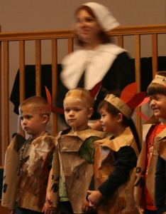 Elementary school kids often dress up as (historically inaccurate) Pilgrims and Indians, with Pilgrims dressed in black and silver buckles and Indians sporting colorful feathers (Creative Commons photo by Flickr user born1945)