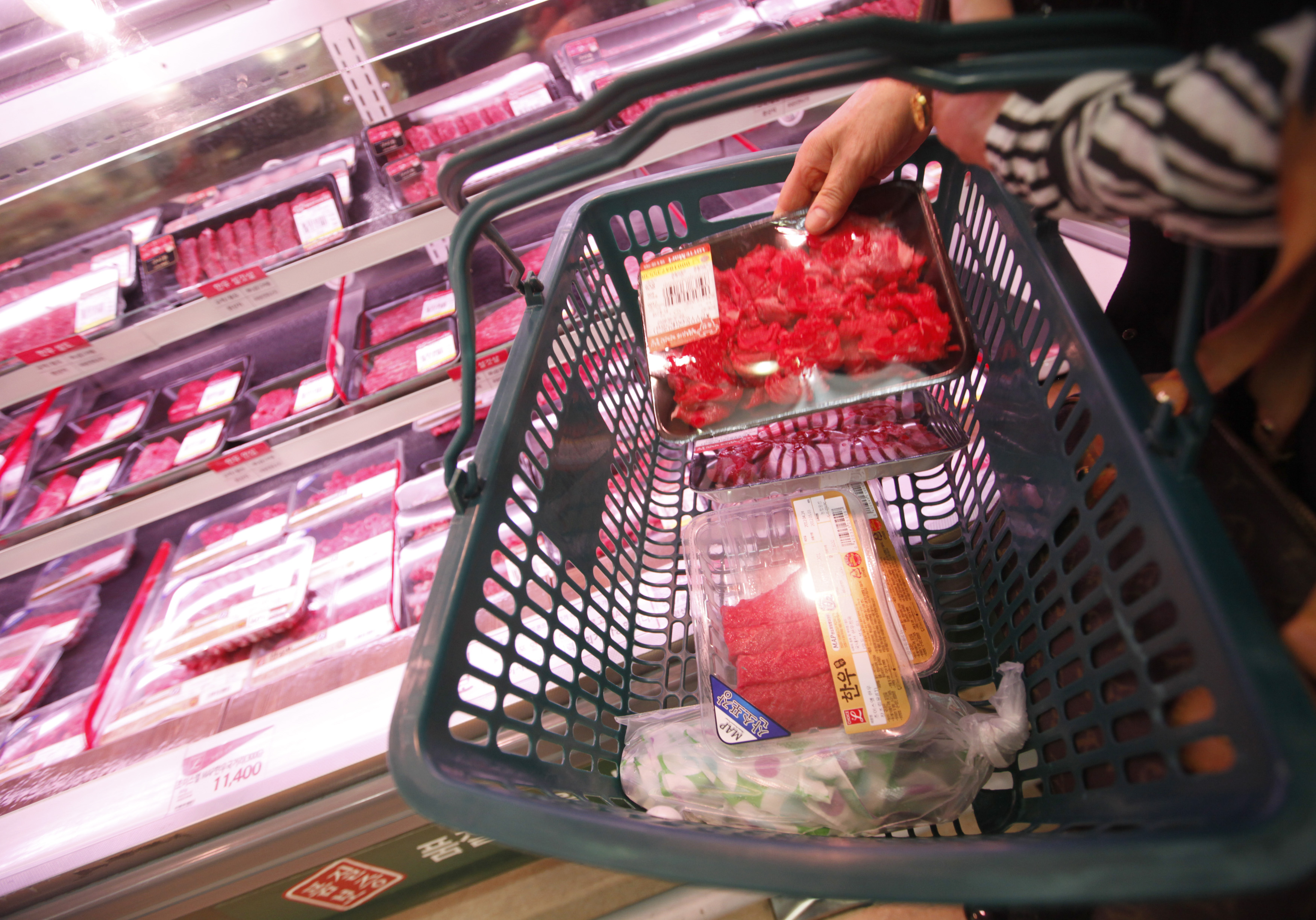 """A woman picks up local beef at Lotte Mart in Seoul April 25, 2012. Two major South Korean retailers halted sales of U.S. beef after an outbreak of mad cow disease as the country's agriculture ministry looked set to move towards banning quarantine inspections, a move that would effectively end imports. Lotte Mart, a unit of Lotte Shopping Co., said it had suspended sales due to what it said was """"customer concerns"""", as did Home Plus, a unit of Britain's Tesco PLC."""