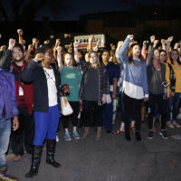 University of Oklahoma students rally outside the now closed University of Oklahoma's Sigma Alpha Epsilon fraternity house  during a rally in reaction to an incident in which members of a fraternity were caught on video chanting a racial slur, in Norman, Okla., Tuesday, March 10, 2015. A moving truck can be seen at rear. Fraternity members were given a midnight Tuesday deadline to be moved out of the house. (AP Photo/Sue Ogrocki)