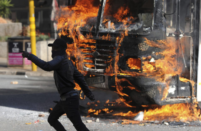 A protesting student runs past a burning bus off campus outside the University of the Witwatersrand in Johannesburg, South Africa on Monday, Oct. 10, 2016. Tear gas and water cannon were fired as hundreds of students protested at the university amid a bitter national dispute with university managers and the government over demonstrators' demands for free education, forcing student into the neighbouring city streets. (AP Photo)
