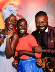 """Actors Lupita Nyong'o (L), Madina Nalwanga (C) and David Oyelowo laugh after posing in the same manner as they appear on the movie poster seen behind him during the Los Angeles premiere of """"Queen of Katwe"""" in Hollywood, California, Sept. 20, 2016."""