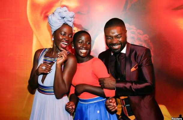 "Actors Lupita Nyong'o (L), Madina Nalwanga (C) and David Oyelowo laugh after posing in the same manner as they appear on the movie poster seen behind him during the Los Angeles premiere of ""Queen of Katwe"" in Hollywood, California, Sept. 20, 2016."