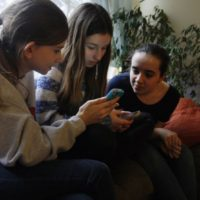 Kate McClintock, 12, left, Kate Green, 13, and Lilly Bond, 13, look at their smartphones at Lilly's home in Evanston, Ill. on Thursday, April 3, 2014. The friends are seventh-graders at Haven Middle School in Evanston, which was at the center of a controversy over its dress code.