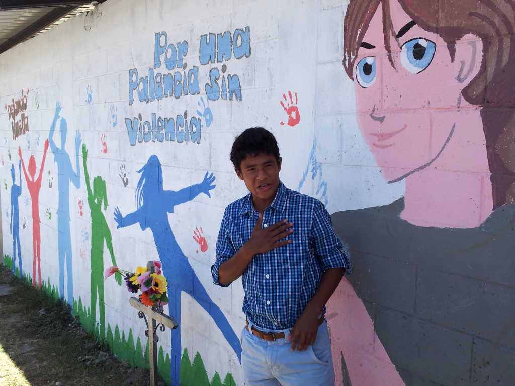 "A youth in Palencia, Guatemala, who painted a mural on the wall in front of a stadium where one of his friends had been killed. The writing says ""For a Palencia without Violence."" (ICMA)"