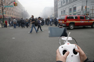 Brian Wilson flies a camera near the scene where two buildings were destroyed in an explosion, in the East Harlem section in New York City, March 12, 2014. (Reuters)