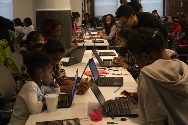 Volunteer teachers work help young students with computer programming at a Black Girls Code class in New York. (Black Girls Code)