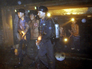 Rescuers help a coal miner out of a flooded mine in China